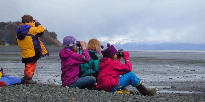 Children_sit_on_the_beach_and_watching_the_horizon_with_binoculars